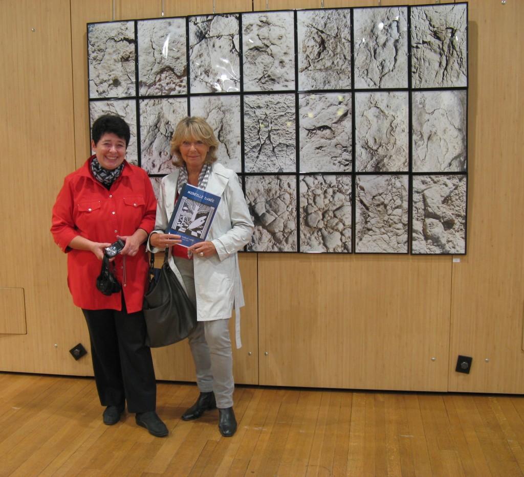 """Mireille Dabée (à gauche), devant l'ensemble intitulé """"Pierres de Palmyre"""" composé de 21 tableaux, fait de sept triptyques verticaux accolés sur trois strates."""